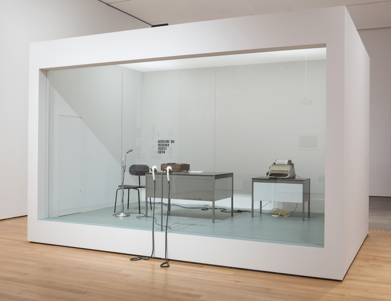 """David Lamelas, """"Office of Information about the Vietnam War at Three Levels: The Visual Image, Text and Audio"""" (1968/2015), office furniture, telex, tape recorder, microphone, telephone receivers, text, Plexiglas partition, and performance"""