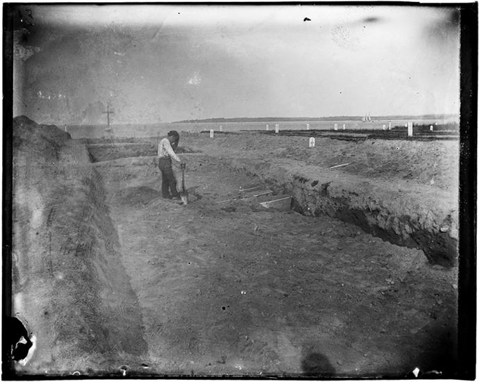 "Jacob Riis, ""The Potter's Field Consecrated Ground"" (1890), gelatin dry plate negative. The image shows a man covering coffins with dirt in an open trench, a burial process mostly unchanged today. (courtesy Museum of the City of New York)"