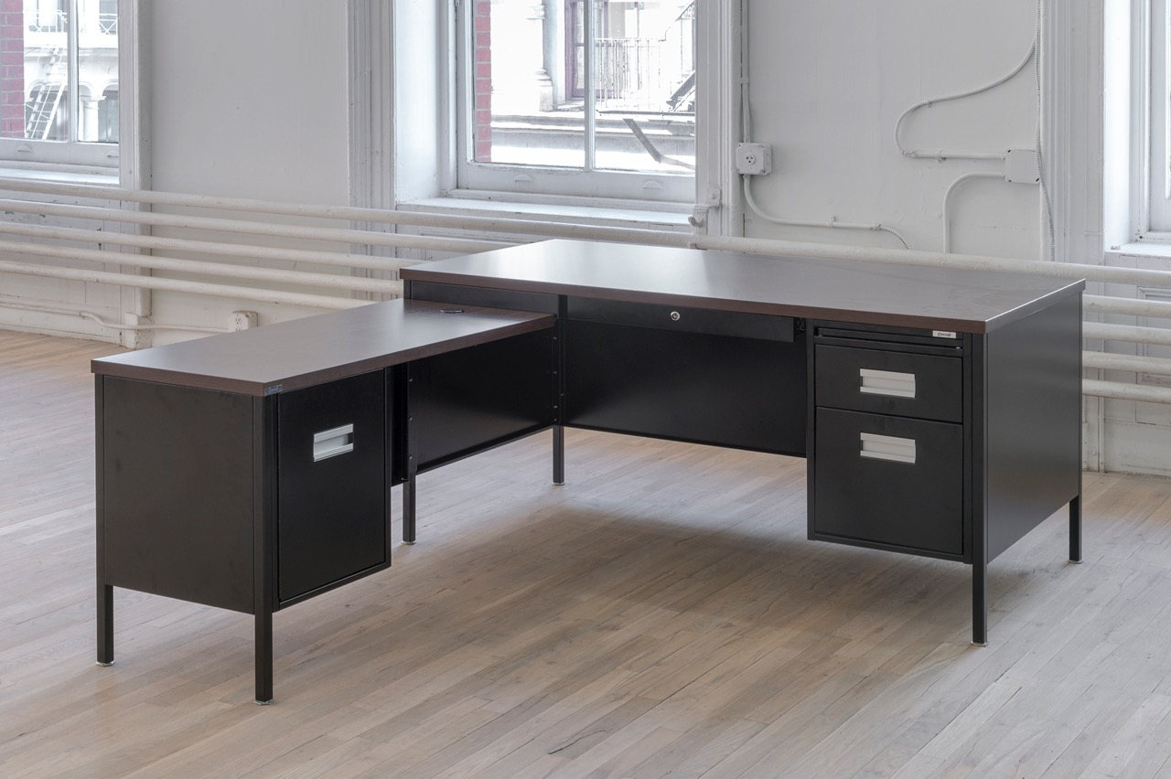 """Attica Series Desk, 2016 Steel, powder coating, laminated particleboard, distributed by Corcraft 60  71.5  28.75 inches Rental at cost The Attica Series Desk is manufactured by prisoners in Attica Correctional Facility. Prisoners seized control of the D-Yard in Attica from September 9th to 13th 1971. Following the inmates' immediate demands for amnesty, the first in their list of practical proposals was to extend the enforcement of """"the New York State minimum wage law to prison industries."""" Inmates working in New York State prisons are currently paid $0.10 to $1.14 an hour. Inmates in Attica produce furniture for government offices throughout the state. This component of government administration depends on inmate labor. Courtesy of the artist and ESSEX STREET, New York Photo: Adam Reich"""