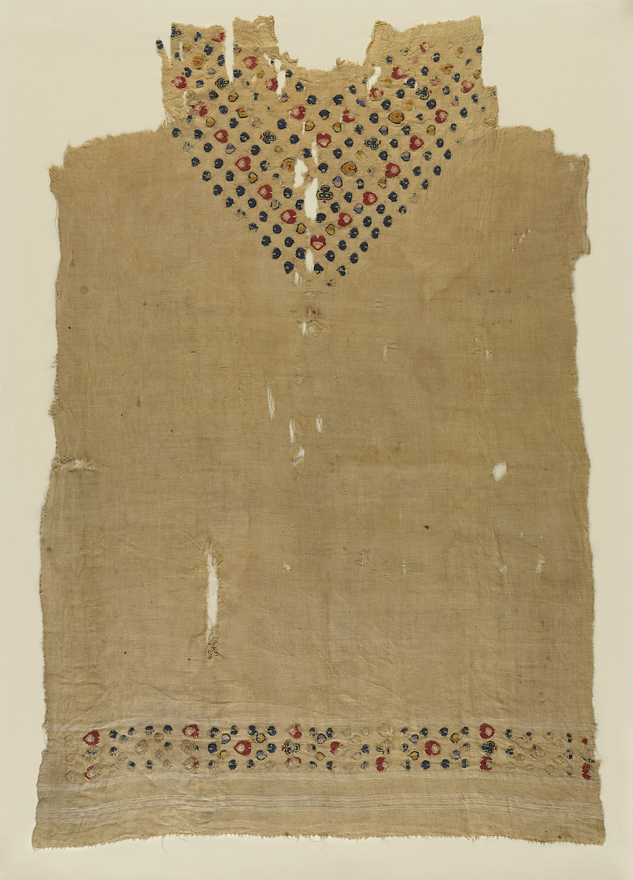 """Tunic with floral motifs at neck and bottom edge, plain (tabby) ground weave, tapestry band of dyed wools of floral motifs at lower edge and forming """"v"""" at neck (Egypt, c5th –6th century CE) (©Brooklyn Museum, photo by Sarah DeSantis)"""