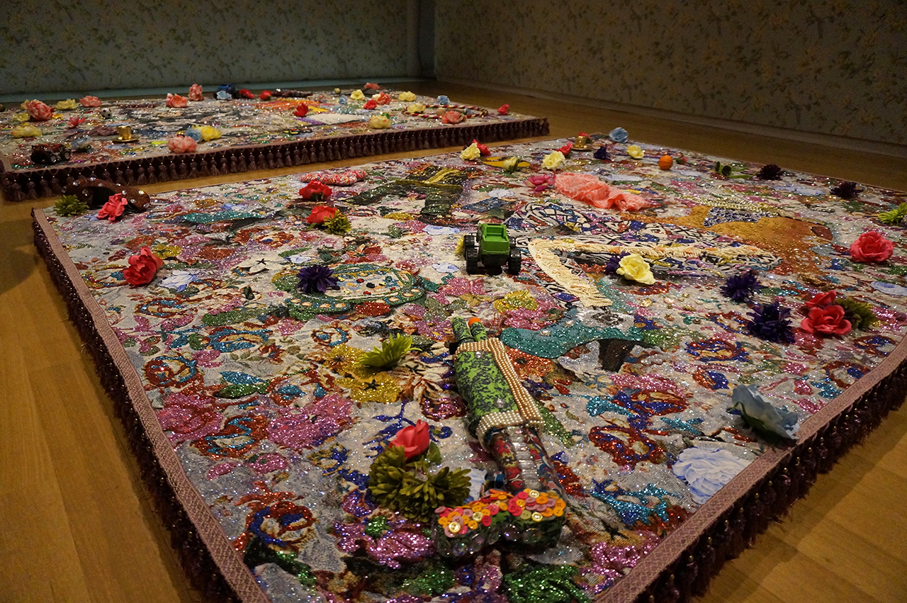 """Installation view, 'Ebony G. Patterson: Dead Treez' at the Museum of Arts and Design; in foreground: """"root and shrubz"""" (2014), mixed-media jacquard photo tapestry with embroidery, glitter, toy gun, shoe, lace, glasses, toys, silk flowers, embellishments (all photos by the author for Hyperallergic) (click to enlarge)"""