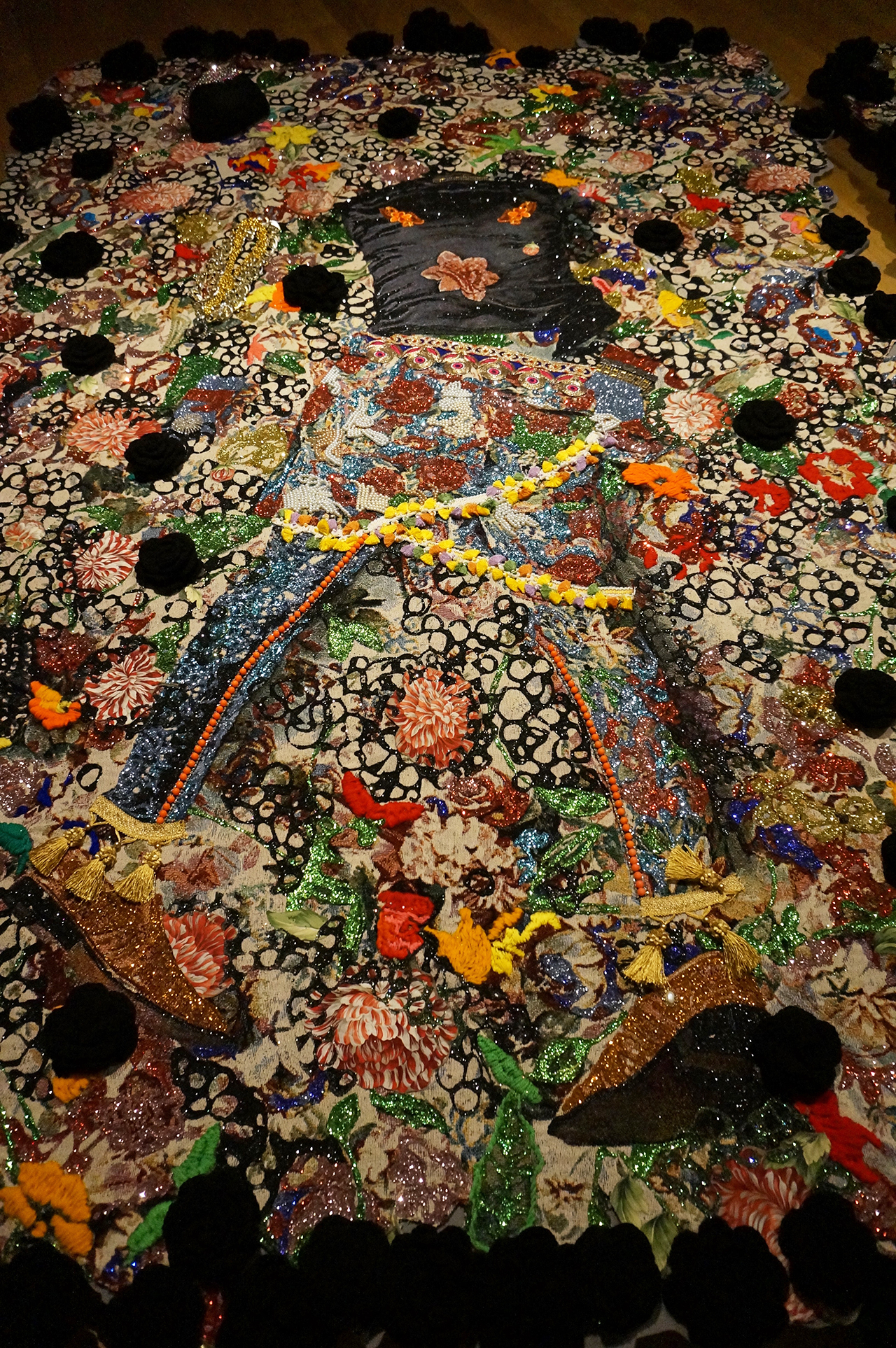 """Detail of Ebony G. Patterson, """"wilted rosez"""" (2014), mixed-media jacquard tapestry, with embroidery, glitter, caftan, costume jewelry, glass, eighty black crocheted flowers, embellishments"""