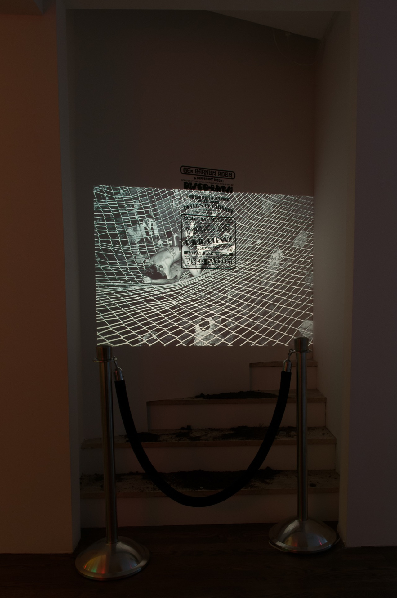 Hilton Als, Dirt Nap/Disco Nap, 2016, dimensions variable, slide projector, black velvet rope with stanchions, GG's Barnum Room poster; Projected slide: Bill Bernstein, GG's Barnum Room, Disco Bats on Net, 1979, dimensions variable, 35mm slide transfer