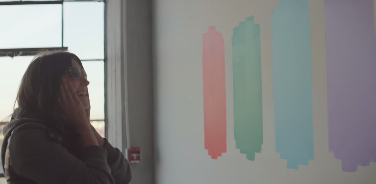 A woman experiences EnChroma's color blindness-correcting glasses, which the report notes are provided to color-blind visitors at the Museum of Contemporary Art, Chicago upon request (screenshot via YouTube)