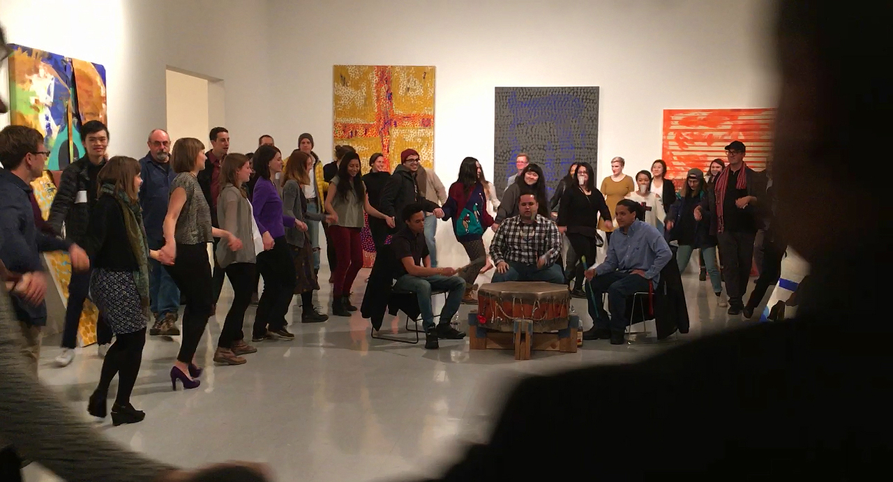 Students, staff, and faculty during the friendship dance; Jason Baerg is on the far right in the hat and scarf (still from video by and © Ardele Lister)