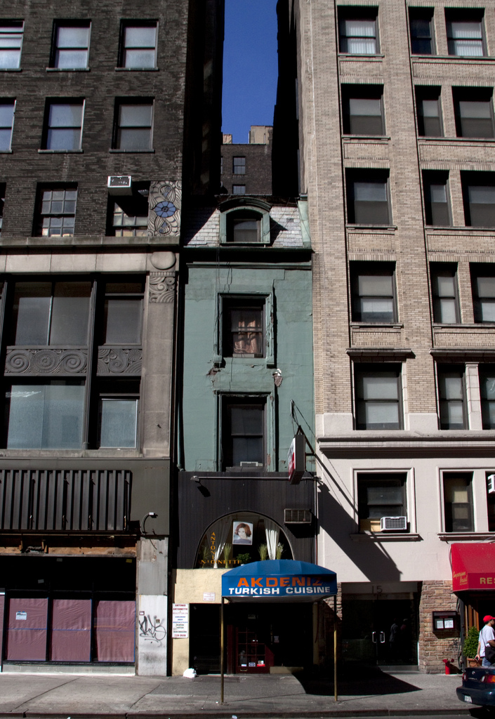 An old building caught between two newer structures in Manhattan (photo by Tony Hisgett/Flickr)