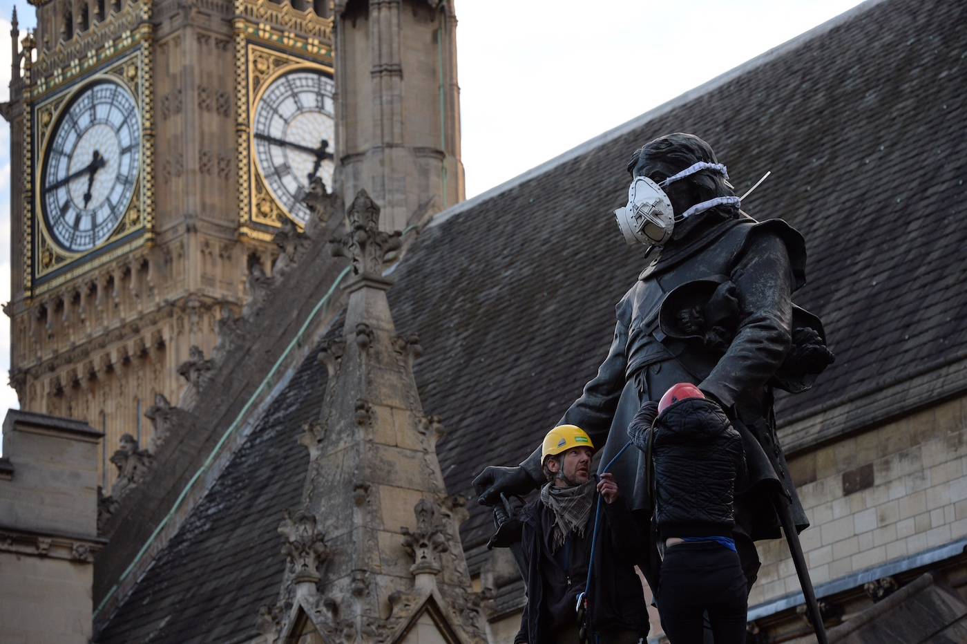Greenpeace activists fit the Oliver Cromwell's statue with an emergency face mask to demand action on air pollution (photo © Chris Ratcliffe / Greenpeace)