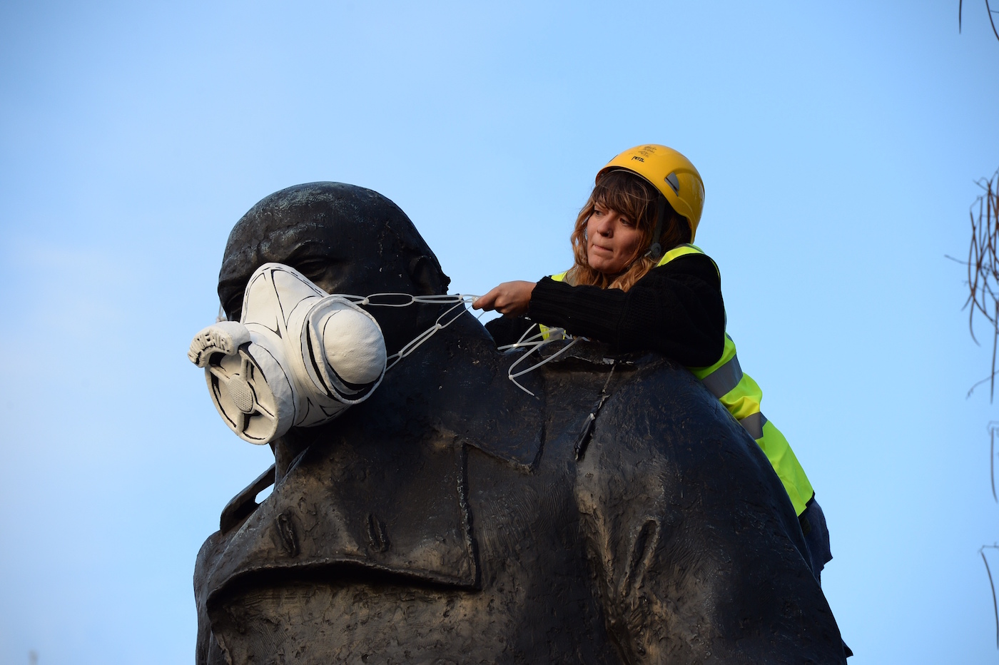 A Greenpeace activist fits the statue of Churchill at Parliament Square with an emergency face mask (photo © Chris Ratcliffe / Greenpeace)