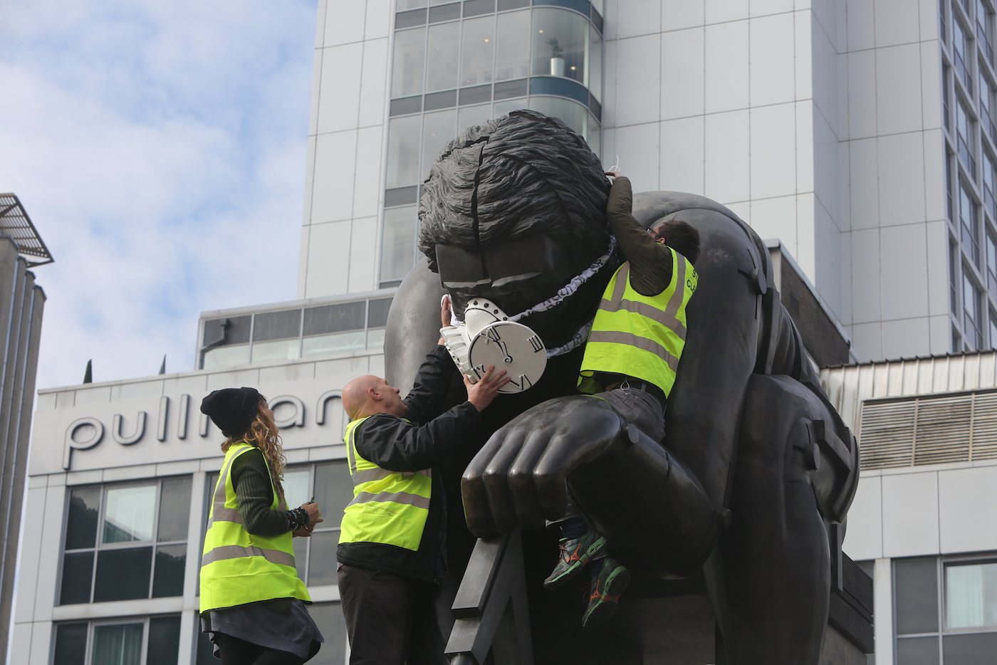 Greenpeace activists fit a statue of Isaac Newton at The British Library with an emergency face mask (photo by John Cobb)