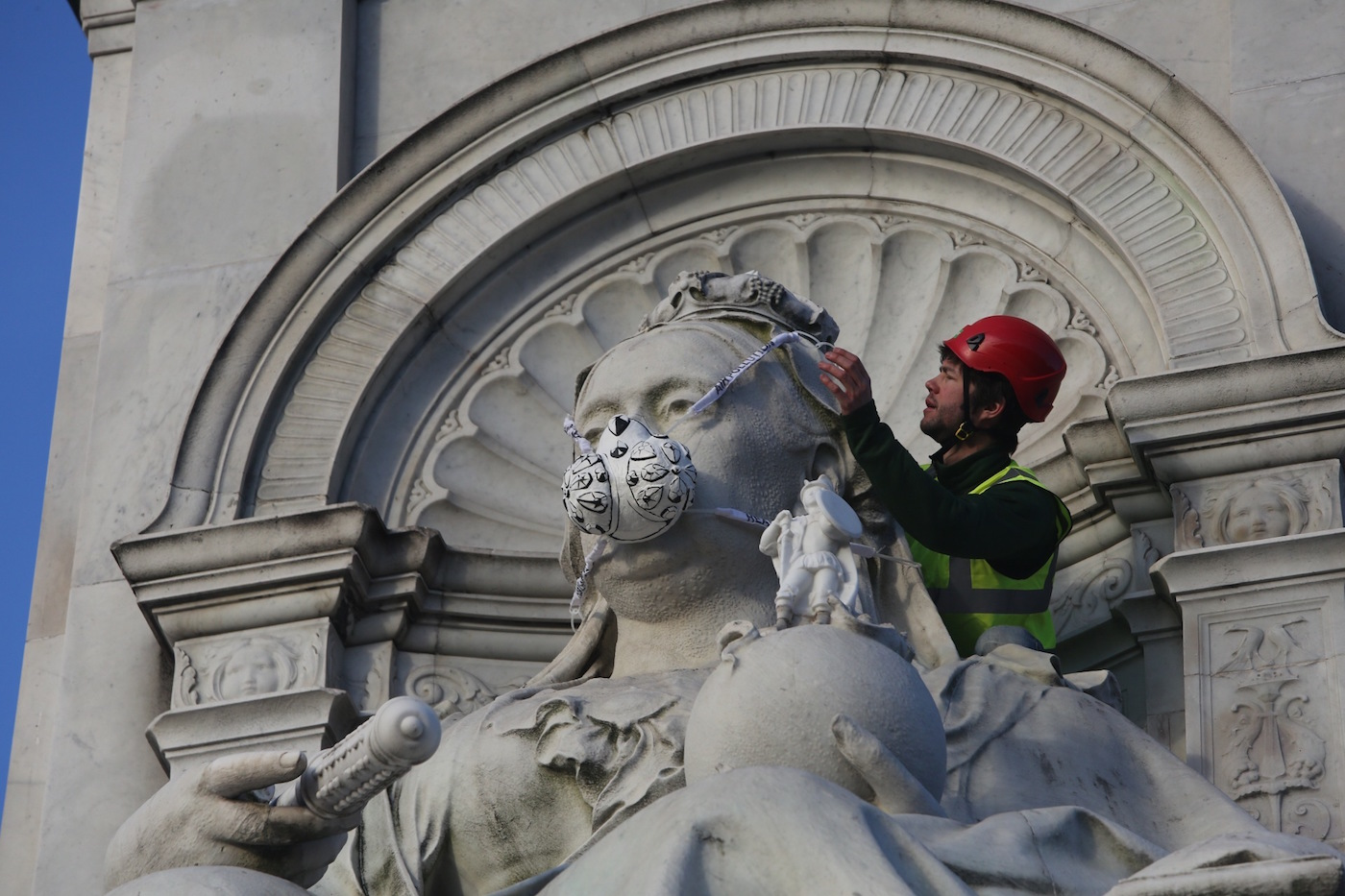 Greenpeace activists fit The Victoria Memorial in front of Buckingham Palace with an emergency face mask (photo by John Cobb)