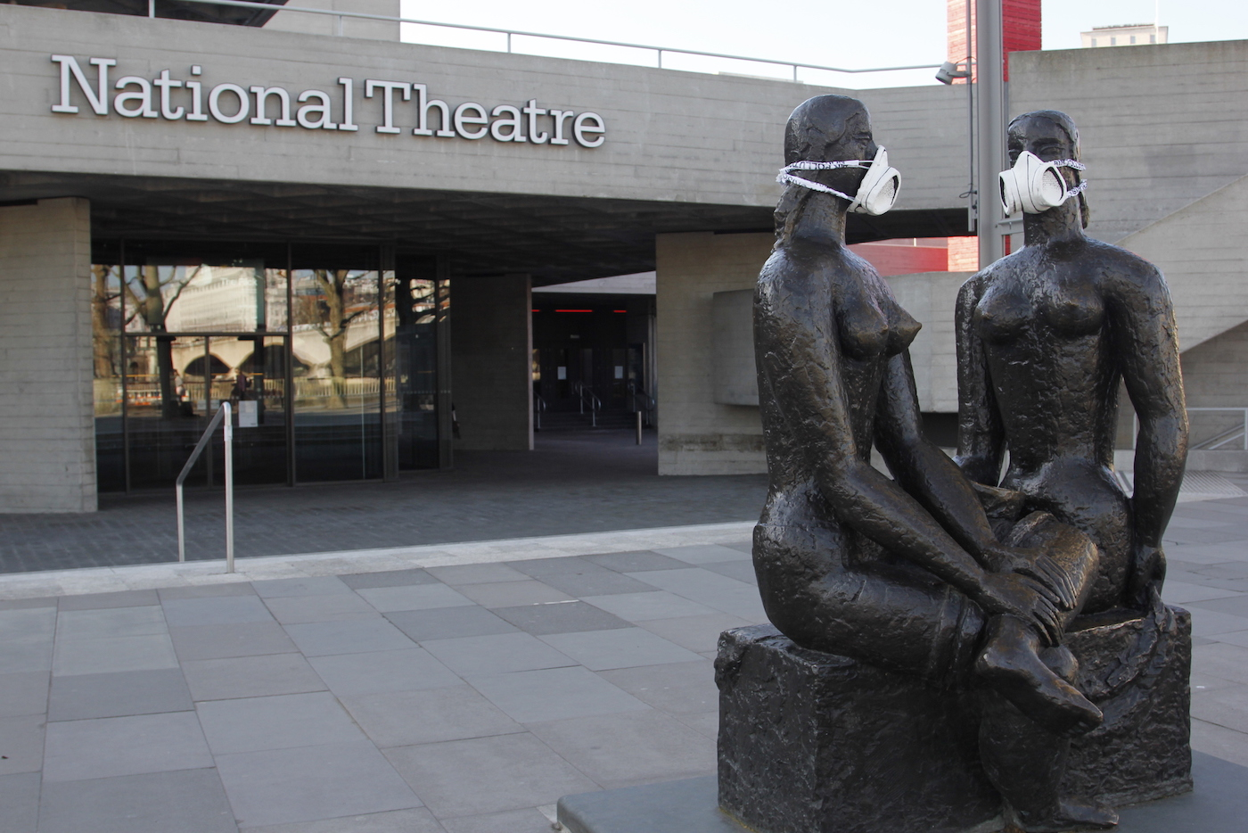 Greenpeace activists fit the London Pride statue, outside The National Theatre, with an emergency face mask