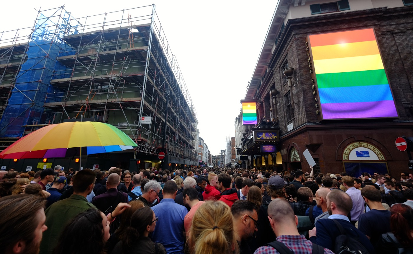 London's vigil in memory of the victims of Orlando's gay nightclub terror attack. Many hundreds of people, some wearing rainbow flags and others carrying placards, came to Old Compton Street in London's Soho district to show solidarity with the victims