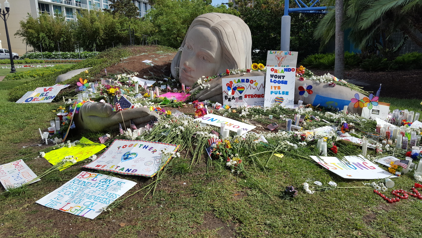 Lake Eola Park in Downtown Orlando on June 20, after the June 19 candlelight vigil. It was said that there were more than 20,000 people in attendance. Candles, flowers, and shrines were all around the lake, and in pockets all throughout the park. (photo by the author for Hyperallergic)