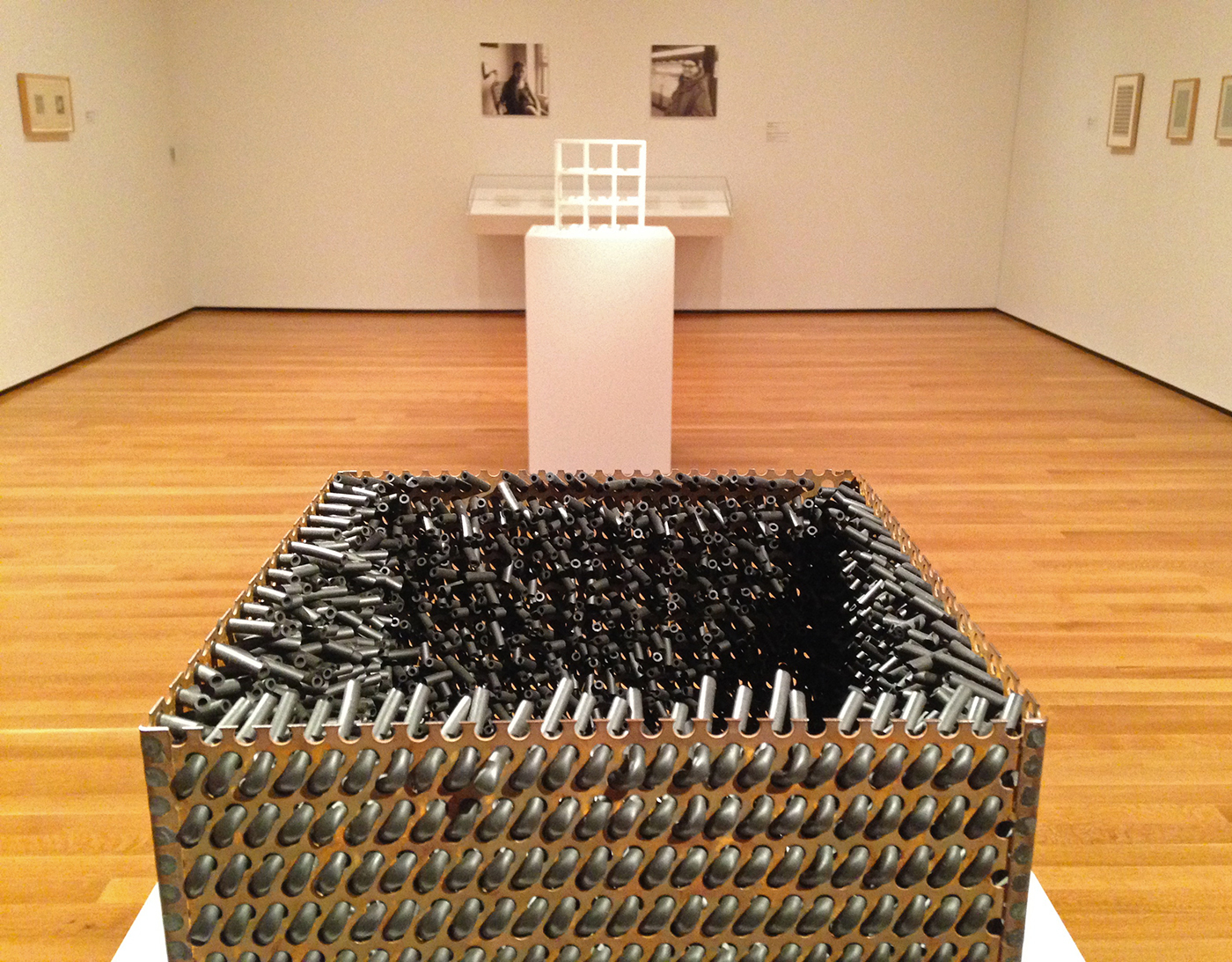 """Foreground: Eva Hesse, """"Accession V"""" (1968), galvanized steel and rubber; background: Sol LeWitt, """"3 x 3 x 3"""" (1965), painted wood"""