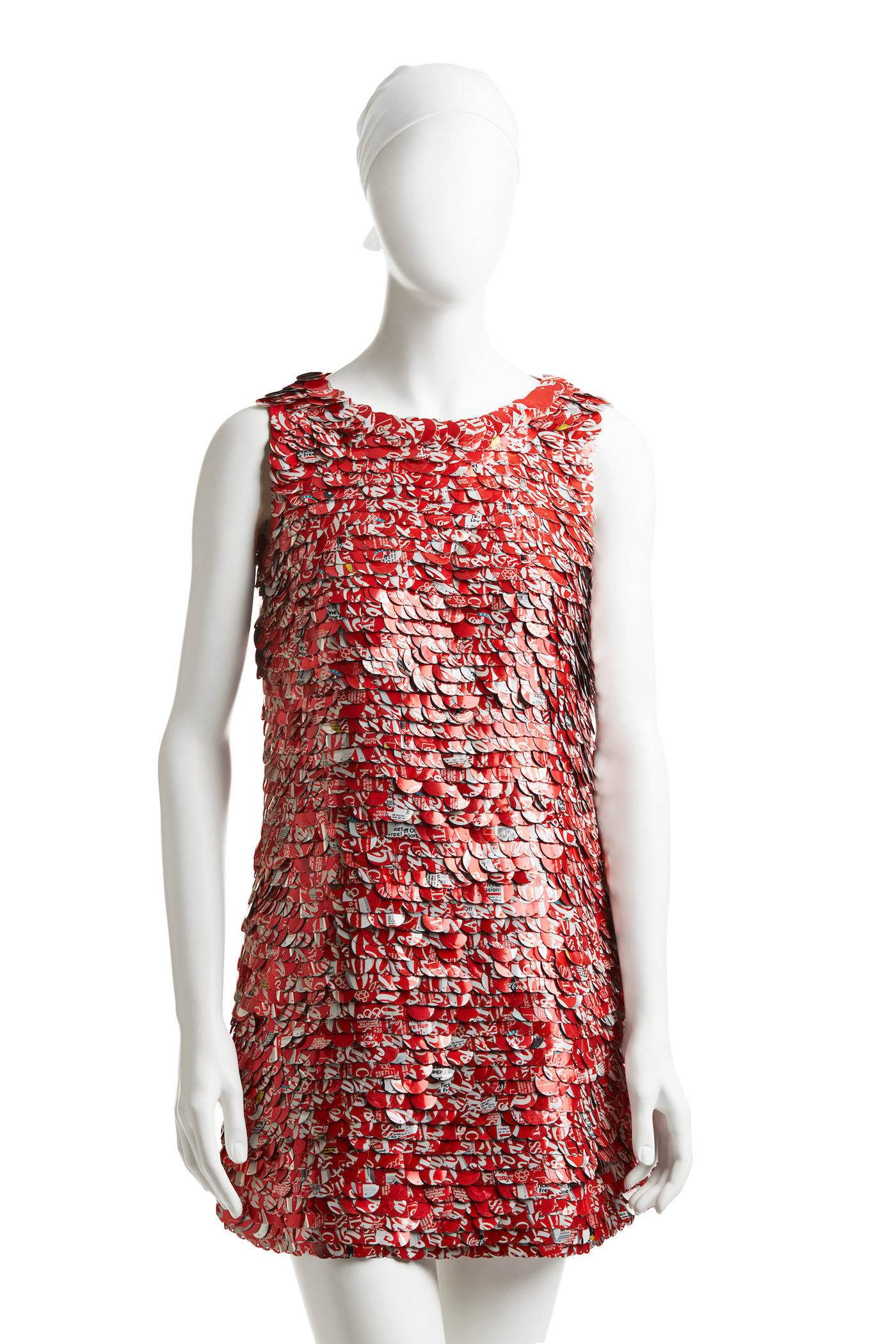 The Real Thing, Coca-Colañcan paillette dress, spring 1994. The Coke can makes an improbable appearance on the runway: Mizrahi used an elaborate process to create these custom paillettes from real Coca-Cola cans. He worked with the charity We Can, which employed homeless New Yorkers to collect cans to recycle; these were shipped to the sequin-maker Langlois-Martin in Paris, where they were cut into paillettes that were then sent to India to be beaded onto dresses. The result is a high-fashion, nearly weightless modern take on a ubiquitous American icon.