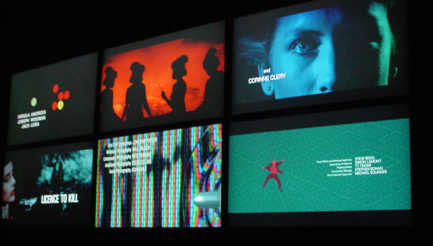 Six screens playing opening title sequences from various James Bond films (photo by the author for Hyperallergic)