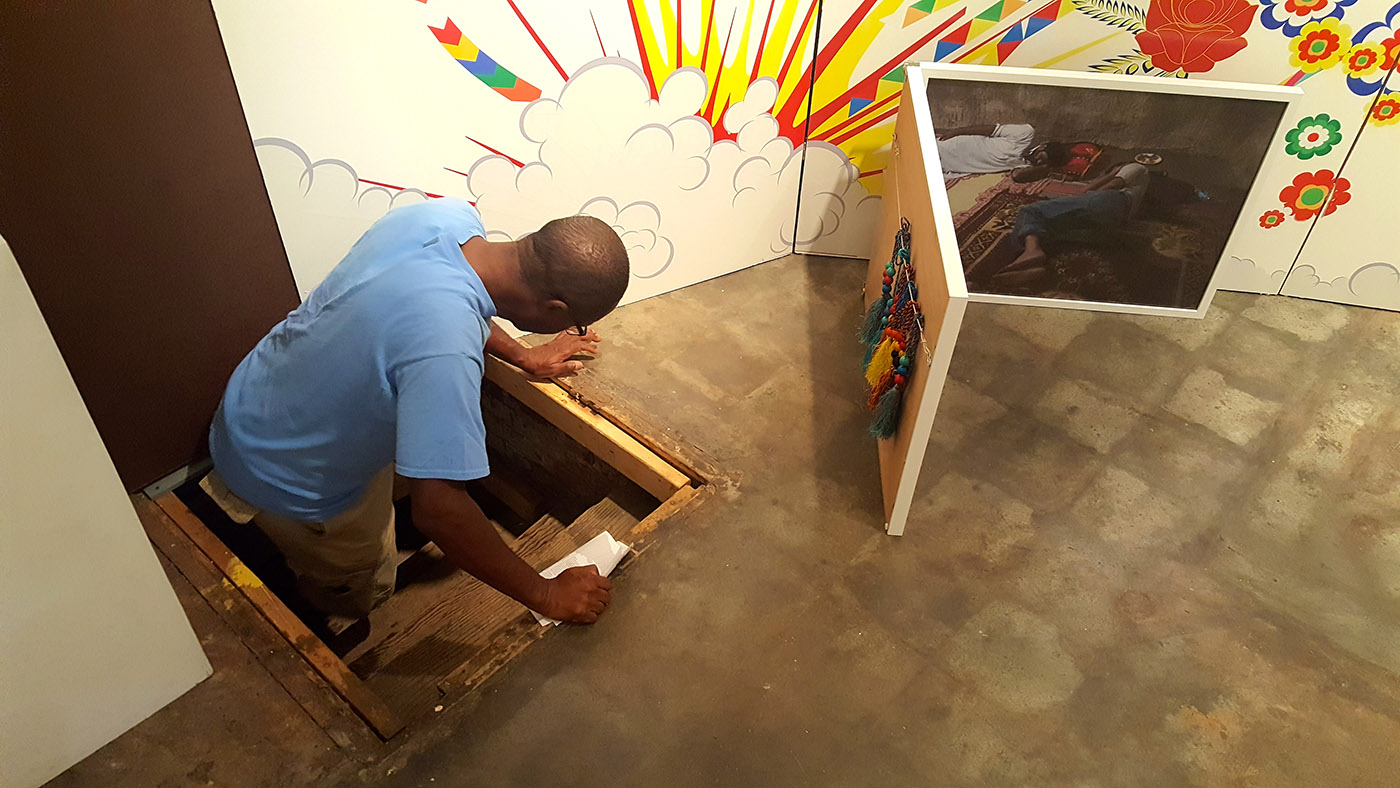 A gallery visitor climbs through the trap door into Khan's inner psyche.