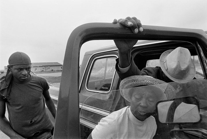 Caption: Porter Lee Davis helps her critically ill husband, Mr. Will, from the cab of their pickup truck. Title: Porter Lee and Mr. Will, Hughes, Arkansas, 1986
