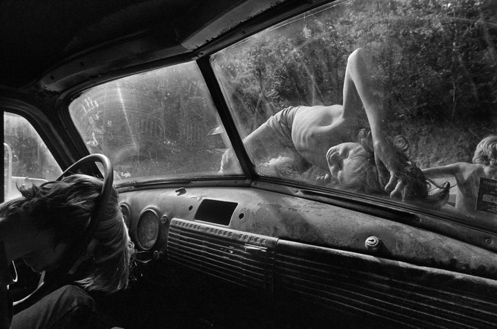 Caption: Boys sleep on the hood of a pickup truck on a hot summer day in Still House Hollow, Tennessee. Title: Still House Hollow, Tennessee, 1986