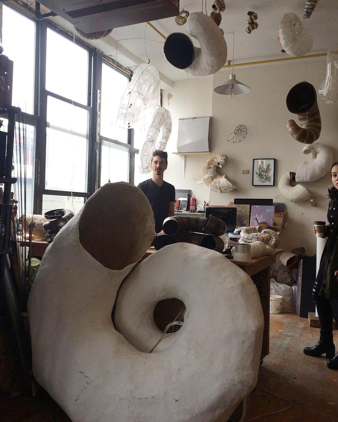 Paulapart amid their sculptures (photo by Claire Voon for Hyperallergic)