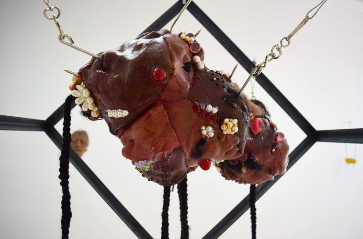 """Doreen Garner, """"Suspension"""" (2016, detail), silicone, pearls, hair weave, speculum, steel cage, steel chain, suspension hooks, 24 x 24 x 24 in; 36-in steel chain"""