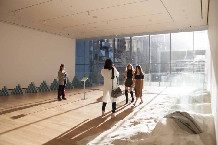 Visitors make their way downstairs to the meditation as sunlight streams through the windows of the Museum of Modern Art.