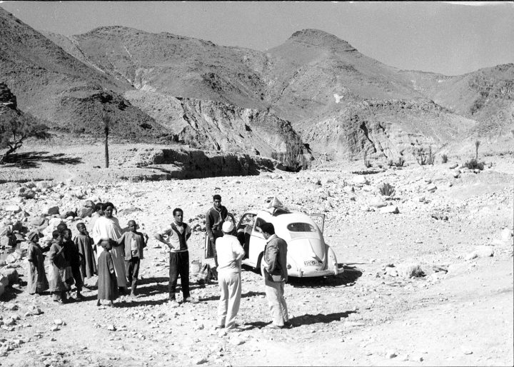 Paul Bowles's VW bug along a Morocco mountain road, with a small group (image courtesy Dust-to-Digital / Library of Congress)
