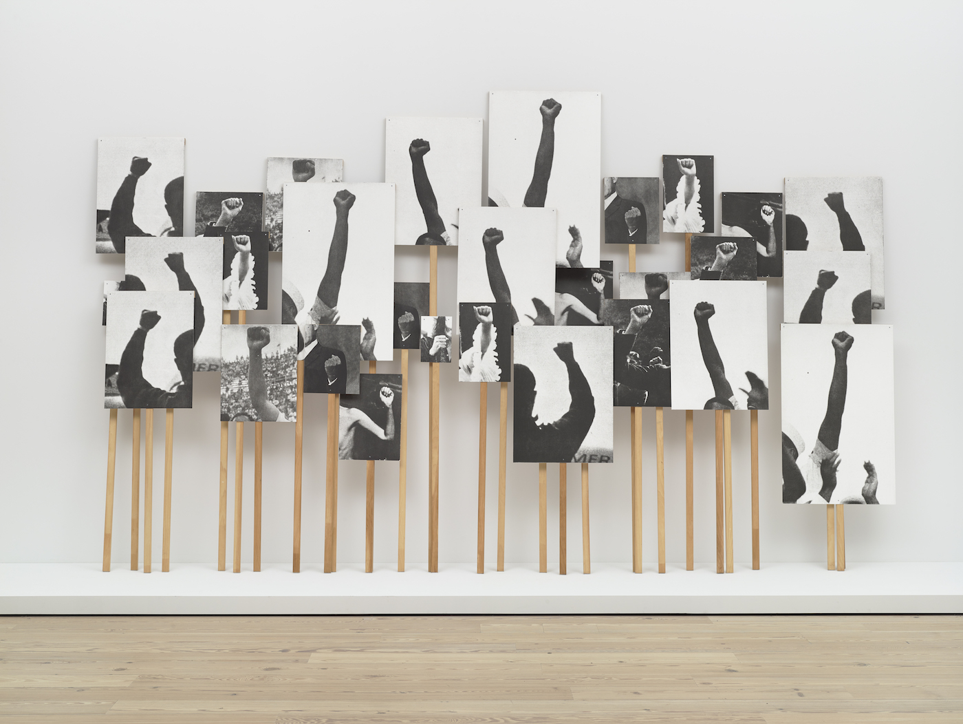 "Annette Lemieux, ""Left Right Left Right"" (1995), 30 photolithographs and 30 pine poles, dimensions variable (Whitney Museum of American Art, New York; purchase, with funds from the Print Committee; courtesy the Whitney Museum of American Art)"