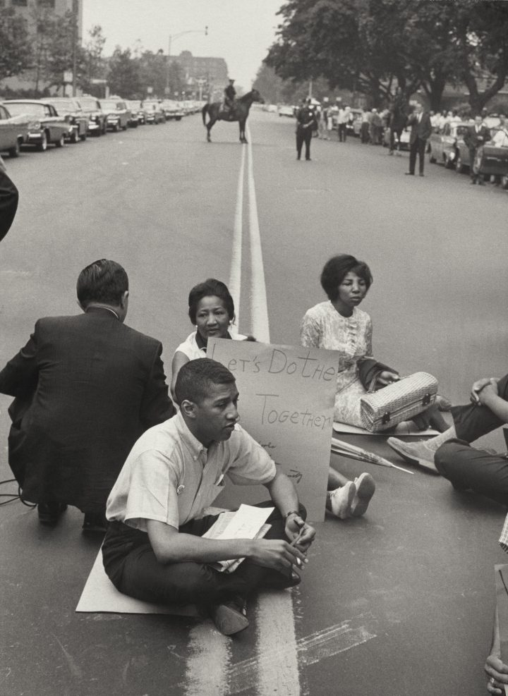 """Leonard Freed, """"Demonstrators sitting with signs and intentionally blocking traffic during protest on car-lined thoroughfare"""" (Brooklyn, New York, 1963) (courtesy J. Paul Getty Museum, © Leonard Freed / Magnum Photos)"""