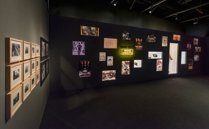 A wall of marketing images relating to New York City-set movies directed by Martin Scorsese, with props and a costume from <em>Gangs of New York</em> (2002) inset in alcoves for <em>Martin Scorsese</em> at the Museum of the Moving Image (photo by Thanassi Karageorgiou, courtesy the Museum of the Moving Image)
