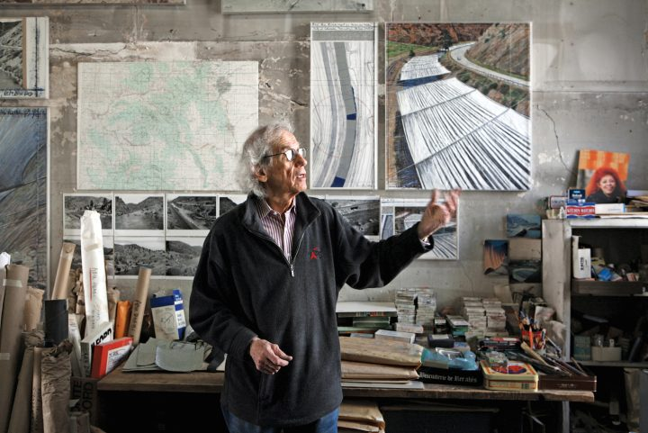 """Christo in his studio with a preparatory collage for """"Over The River,"""" 2011 (photo by Wolfgang Volz, © 2011 Christo)"""