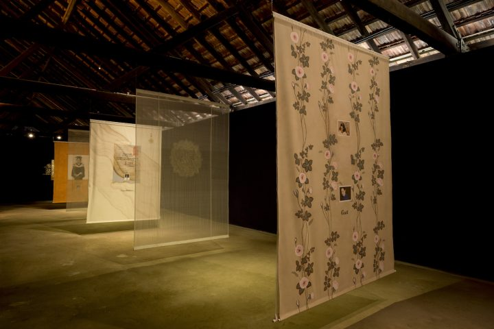 """Desmond Lazaro, """"Family Portraits"""" (2016), installation with hanging cloth, small paintings, video (5:07 minutes), icon with gilded gold leaf"""