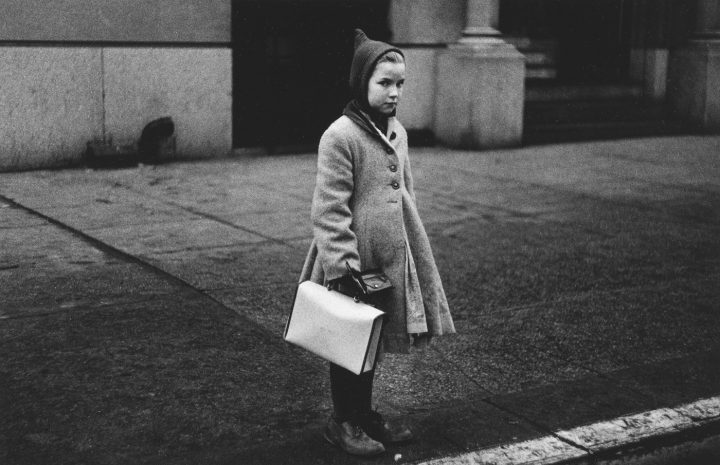 """Diane Arbus, """"Girl with a pointy hood and white schoolbag at the curb, N.Y.C."""" (1957) (courtesy The Metropolitan Museum of Art, New York; copyright © The Estate of Diane Arbus, LLC; all rights reserved)"""