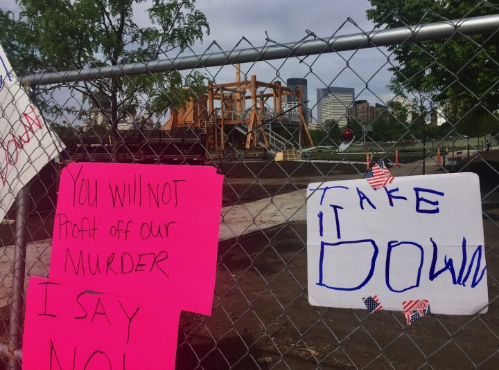 """Protest signs on the fence near Sam Durant's """"Scaffold"""" (2012) in the Minneapolis Sculpture Garden"""