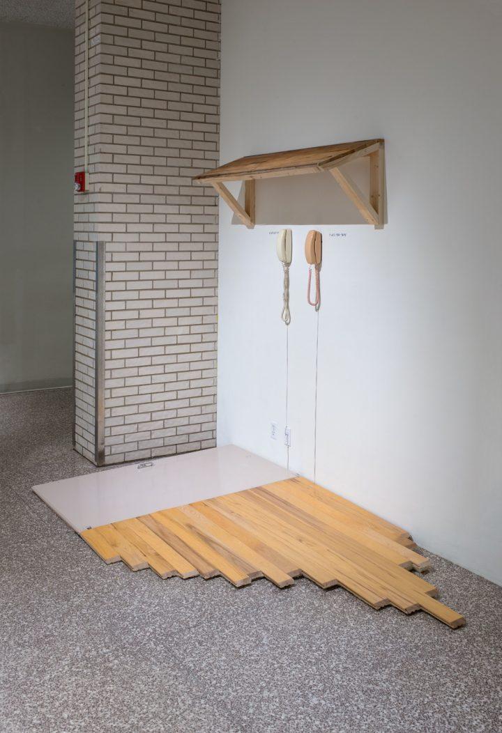 Emmett Ramstad, U201cCalling Station IIu201d (2016) ADA Sanctioned Bathroom Stall  Door, Maple Flooring, Foam, Cedar Awning, Landline Princess Telephones, ...