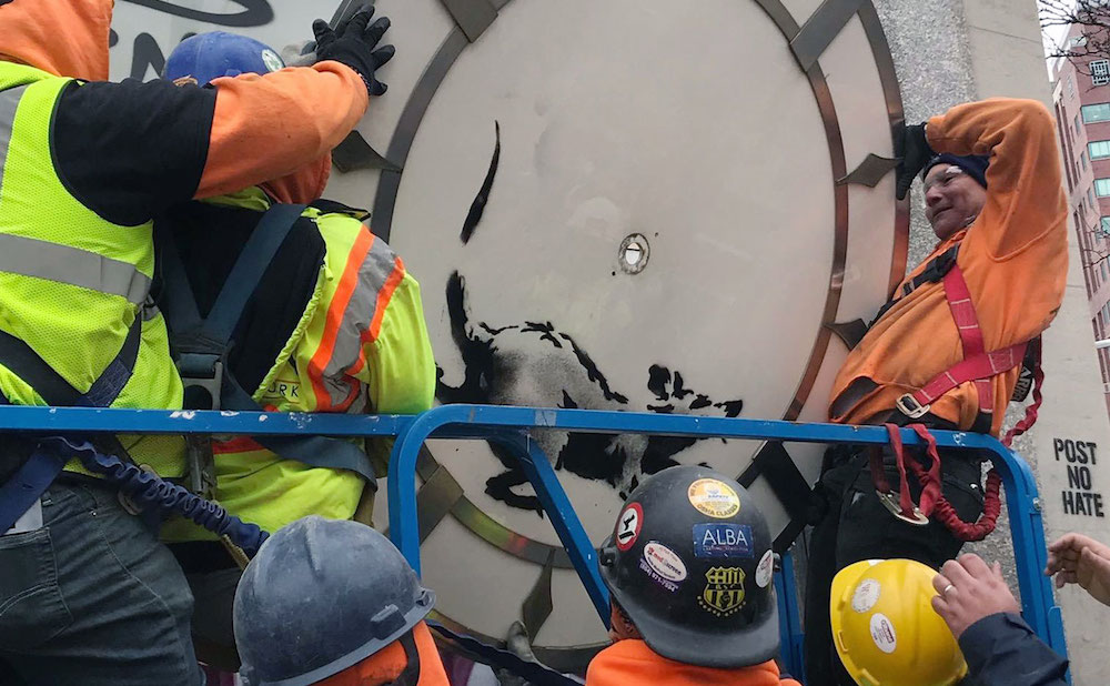 Workers taking down the Banksy at 14th Street and Sixth Avenue in Manhattan (photo by Melissa Stern for Hyperallergic)