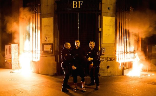 """Petr Pavlensky being detained at the scene of his piece, """"Lighting,"""" in Paris."""
