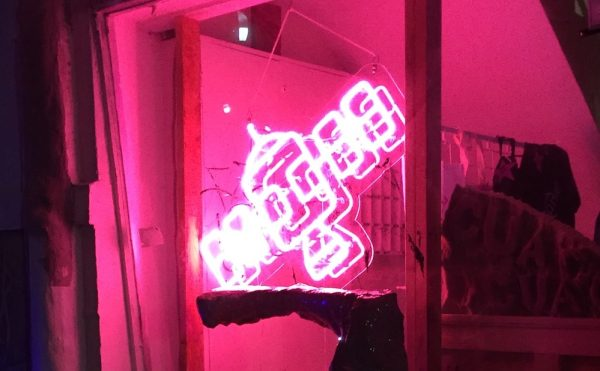 A neon sign of the Satellite Art Show logo at the 2017 edition of the fair