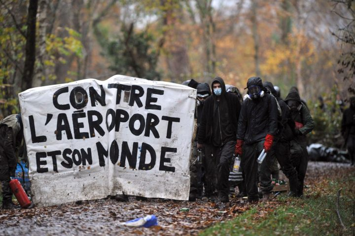 """ZAD residents stand behind a barricade that reads """"No to the airport and its world.""""(photo courtesy John Jordan)"""