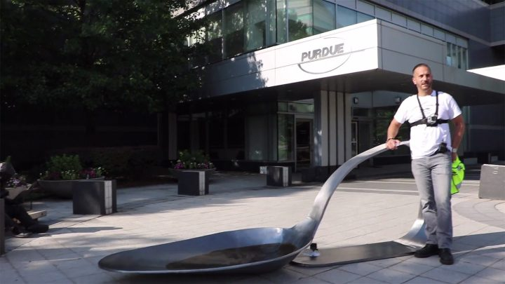 Artist Domenic Esposito stands beside an 800-pound forged steel sculpture of a burnt heroin spoon, following a guerrilla installation outside the headquarters of Purdue Pharma, makers of OxyContin. (all images pulled from live footage of the intervention, courtesy of Fernando Luis Alvarez Gallery)