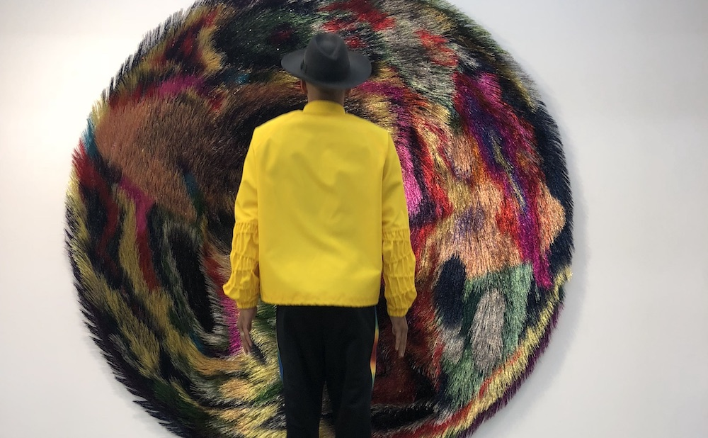 Swizz Beatz in front of a work from Nick Cave's Tondo series (photo courtesy the Dean Collection)
