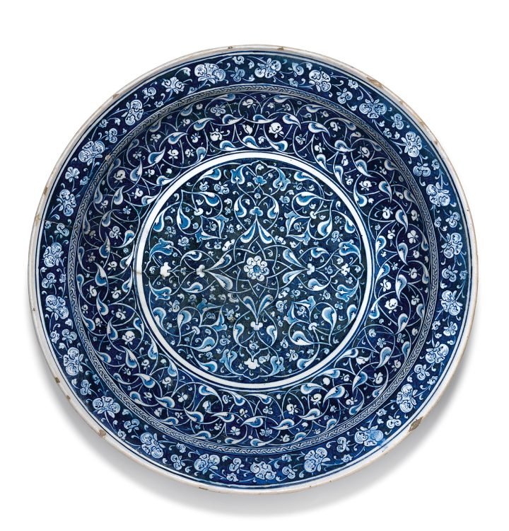 A highly important blue and white Iznik pottery charger, Turkey (c. 1480), of large, deep, rounded form, with an everted flat rim, the interior decorated in reserve within a central roundel against a blue-black ground with an intricate arabesque of interlacing split-palmette 'rumi' motifs in two shades of blue and white emanating from a small central rosette, the cavetto displaying a thick band of corresponding design surmounted by a thin band of interlocking key fret motifs, the flat rim ornamented with a band of scrolling floral 'hatayi' flowers in white, the reverse decorated with a wide band of 'hatayi' lotus scrolls in blue on a white ground, thin double blue lines and a single bracketed line embellishing the underside of the rim, 44.5 cm. diameter, 8.3 cm. depth (image courtesy Sotheby's)