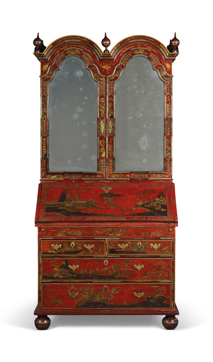 A George II red, silver, and gilt-Japanned bureau cabinet (c. 1730), double-domed top with turned finials above a pair of mirrored doors enclosing an adjustable shelf, pigeon holes and six small drawers and with a pair of candle slides, the fall front revealing a fitted interior with further pigeon holes, open shelves and five drawers above a red leather-lined writing-surface and a well, with two short and two long drawers below, on turned feet, restorations and replacements, 86 ½ inches high, 43 ½ inches wide, 23 inches deep (image courtesy Christie's)