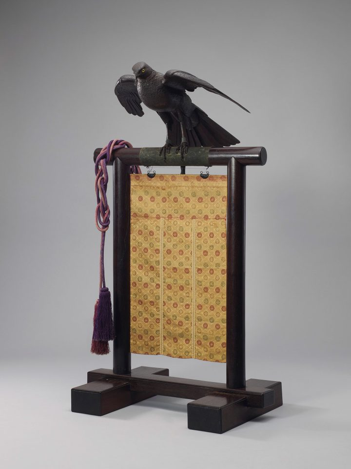 An important iron articulated sculpture of an eagle on stand, Meiji period (c. 1894), 19 3/8 inches long without stand, with original wood box, stand, and brocade curtain (image courtesy Christie's)