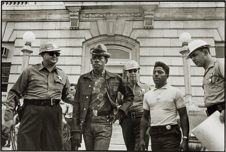 """Danny Lyon, """"Sheriff Jim Clark arrests two SNCC voter registration workers on the steps of the federal building, Selma, Alabama"""" (1963), printed later, gelatin silver print, 11 x 14 inches, San Antonio Museum of Art, gift of Ernest Pomerantz and Marie Brenner (©Danny Lyon/Magnum Photos)"""