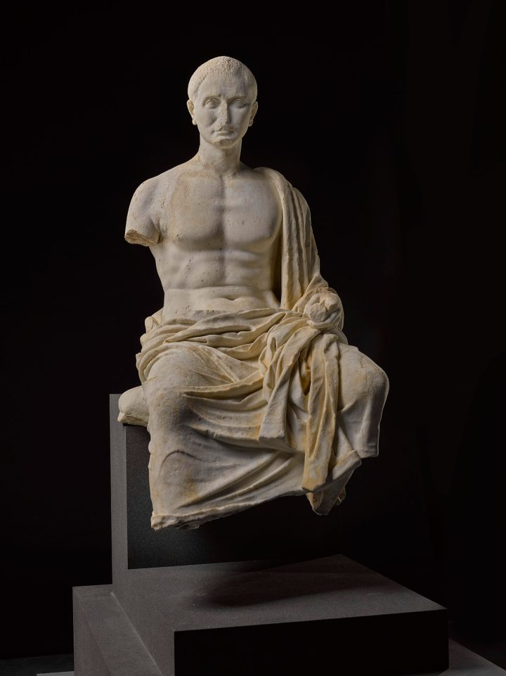 A marble funerary portrait statue of a Roman poet, late Republican/Augustan, 2nd half of the 1st Century BCE, composed of two parts joined at the hips and hollowed out, seated on a cushion in a contemplative attitude and holding a scroll in his left hand, a signet ring on his left hand, his himation draped over the lower part of his body, left shoulder, and left forearm, his head turned slightly to his right, the face with high cheek-bones, fragmentary aquiline nose, deep-set eyes, and furrowed brow, his short cropped hair radiating from the crown, his right foot formerly dowelled on, right shoulder restored, height 115 cm., height of head 25 cm. (image courtesy Sotheby's)