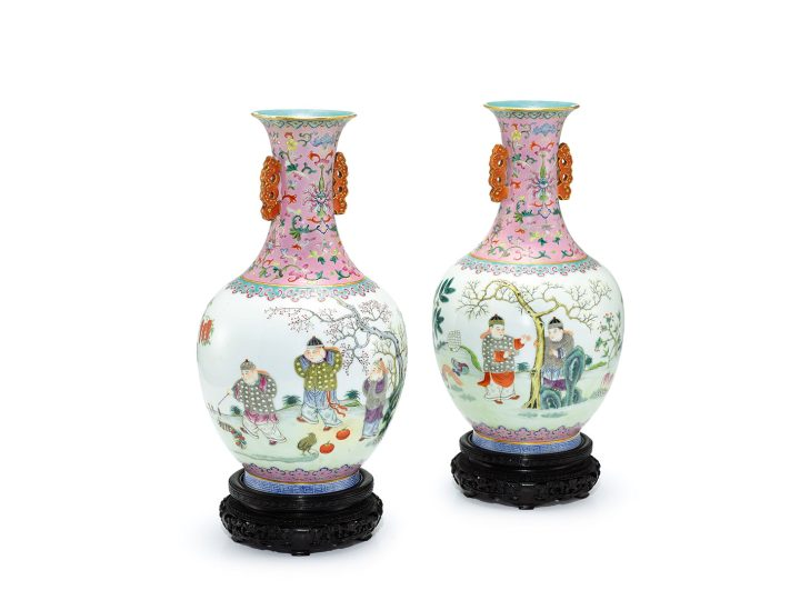 """A rare pair of pink-ground famille-rose """"Boys and Firecrackers"""" vases. Shendetang Hall Marks, Qng Dynasty, Daoguang period, each well-potted with an ovoid body rising from a short splayed foot to a tall waisted neck and flaring rim, the neck flanked by a pair of stylized dragon handles with gilt highlights, the exterior of the body enameled with a continuous scene, depicting five boys dressed in lavish winter clothing and lighting firecrackers in a garden laden with ripe fruits and lingzhi, all between a pink-ground and a turquoise-ground ruyi-band, the neck decorated with lotus scrolls and bats against a pink ground, the interior and base enameled turquoise, the base inscribed in iron-red with a four-character Shendetang zhi hall mark, wood stands, 11 3/4 inches (image courtesy Sotheby's)"""
