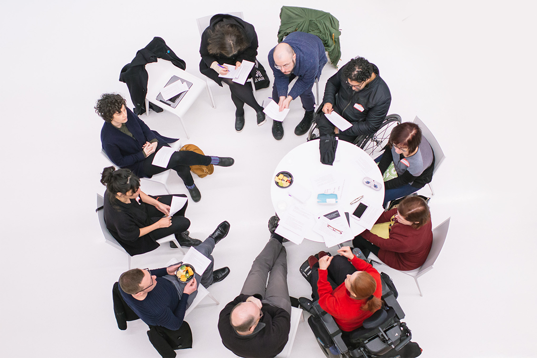 From above, disabled artists and activists form a circle around a table against a white floor.