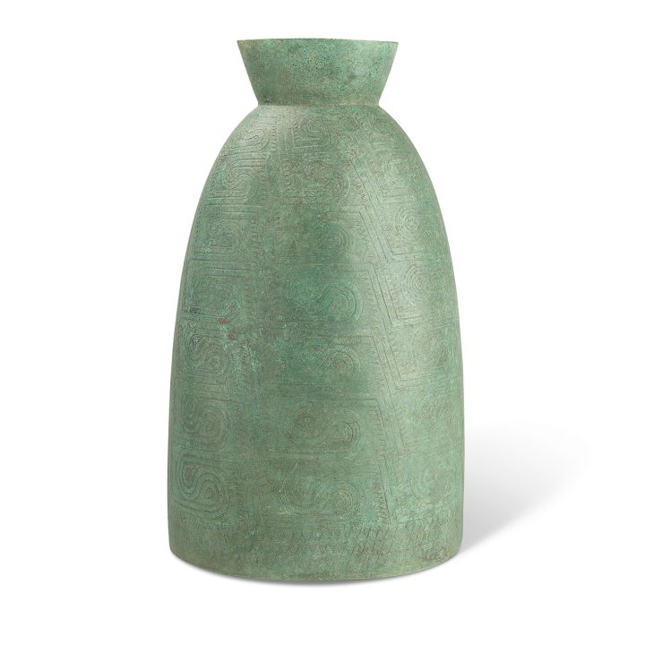 A Cambodian bronze ceremonial bell, Battambang Province, probably 2nd century BCE to 2nd century CE, of waisted oval section, decorated overall with geometric scrolls in low relief, 22 3/4 inches high, 13 inches wide, 10 3/4 inches deep (image courtesy Christie's)
