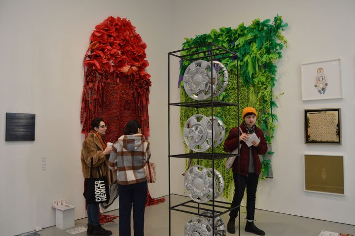 """Borinquen Gallo, installation shot; left: """"Deadly Poppy Field"""" (2016), caution tape, plastic bags, debris netting, ink; right: """"Green Unplugged"""" (2016), caution tape, plastic bags, debris netting, URL cables; center: """"Heaven Wheels Above You"""" (2018–19), cast architectural details, found auto rims, Bondo, paint; Burning in Water gallery"""